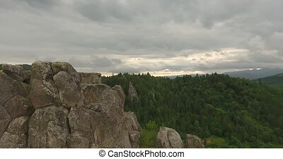 Fly Over Rocks above Forest an Mountains