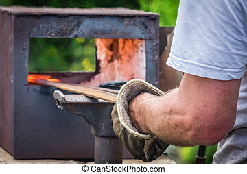 Hot temperature furnace - A blacksmith inserting steel rods...