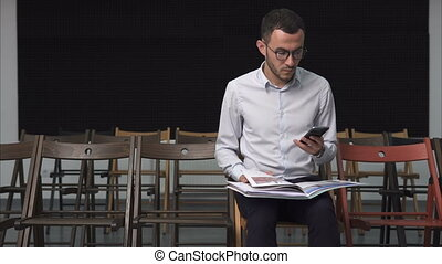 Young businessman looking at documents and holding a smartphone