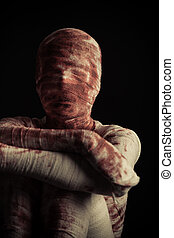 Creepy blood spattered mummy sits in darkness with arms...