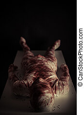 Bloody gauze covered young mummy in darkness displayed on...
