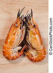 two of shrimp grilled on wood plate