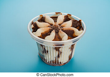 cup of chocolate flavor ice cream on blue cloes up