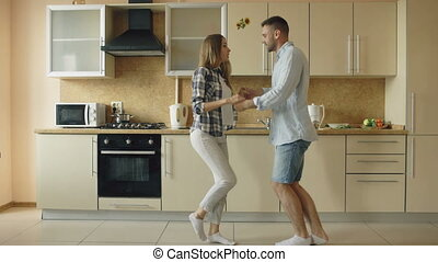 Happy young joyful couple have fun dancing while cooking in the kitchen at home