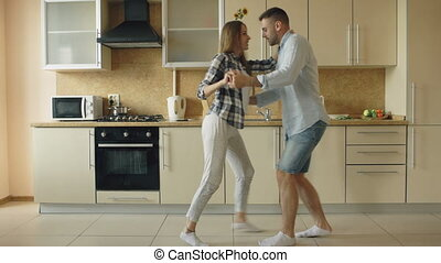 Attractive young joyful couple have fun dancing while cooking in the kitchen at home