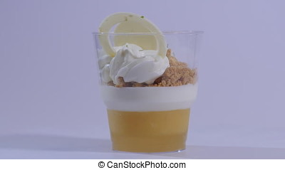 Sweet dessert in glass with biscuit, whipped cream on white...