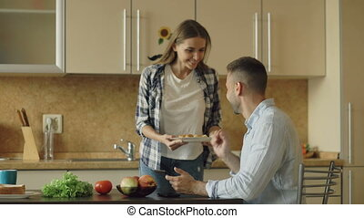 Attractive couple in the kitchen. Man playing surfing tablet computer while his girlfriend feeding him