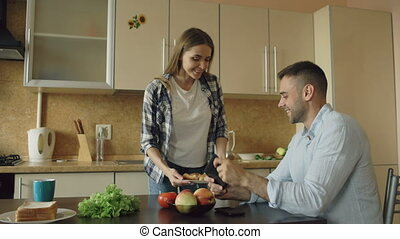Attractive couple in the kitchen. Man playing video game on tablet while his girlfriend feeding him