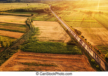 Beautiful aerial view of countryside and fields in sunset -...