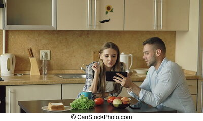Attractive couple using tablet computer fo social media and having breakfast in the kitchen