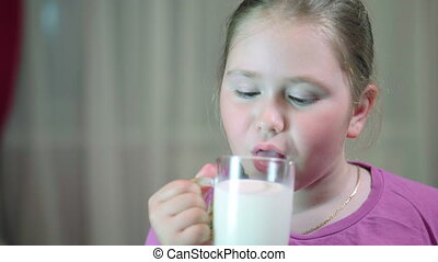 Child drinking milk from glass. Girl with beautiful blond...