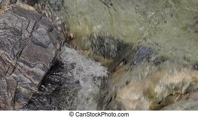 Water in a mountain river in slow motion video.