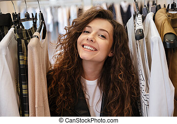 Curly cheerful young lady choosing clothes. - Image of curly...