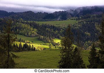 A sunbeam illuminates a valley in the mountains - The...