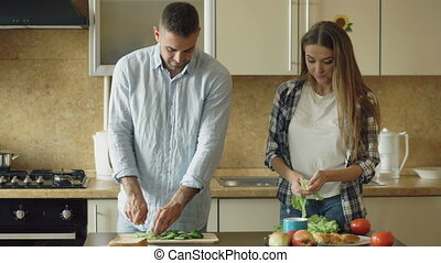 Happy young couple cooking breakfast together in the kitchen eartly morning