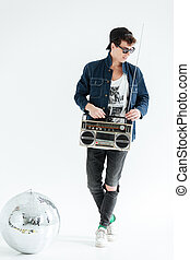 Cheerful young man holding boombox near disco ball. - Image...