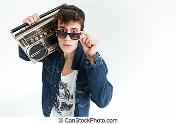 Handsome young man wearing glasses holding boombox - Picture...