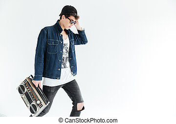 Attractive young man wearing glasses holding boombox. -...