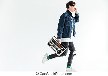 Attractive young man holding boombox. Looking aside. - Image...