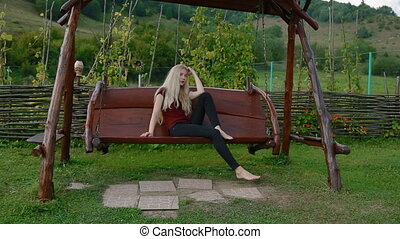 Young woman take a rest on the big woode swing on the...