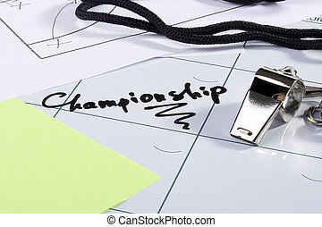 Championship - A silver whistle laying on a calendar with...