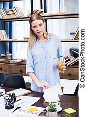 Attractive young businesswoman holding glass with iced tea while standing at desk with papers