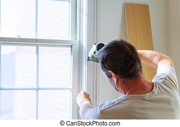 Carpenter using nail gun to moldings on windows, framing...