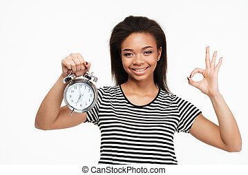 Afro american woman holding alarm clock and showing ok...