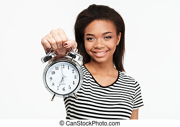 Portrait of a happy african teen girl showing alarm clock -...