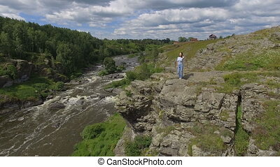 Anonymous woman standing on rocks above river