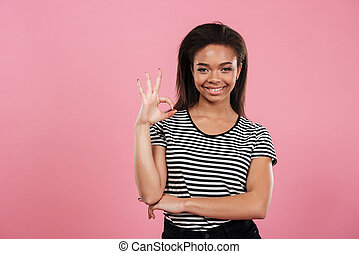 Portrait of a casual afro american woman showing ok gesture