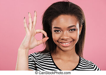 Portrait of a satisfied smiling african woman showing ok gesture
