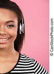 Cropped image of a happy smiling teen girl in headphones...