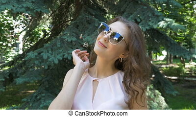 Portrait of a young girl in sunglasses. Which flirts and...