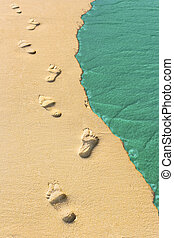 Foot steps and surf on tropical beach, abstract travel...