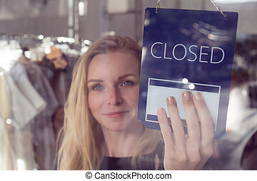Shop worker with the open and closed sign