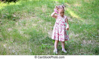 Cute little girl is blowing soap bubbles in the park outdoors on a sunny day.