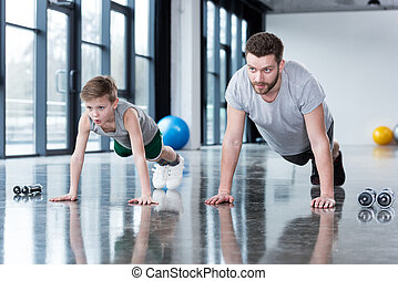 Man and boy doing push ups at fitness center