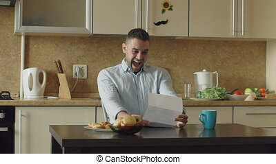 Slow motion of Handsome man recieve good news reading letter in the kitchen while have breakfast at home