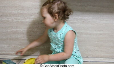 Funny baby helps mom clean up in the kitchen. Dresses rubber...