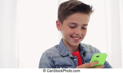 happy smiling boy with smartphone at home