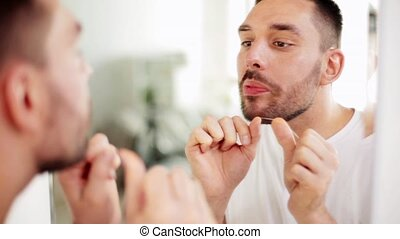 man with dental floss cleaning teeth at bathroom - dental...