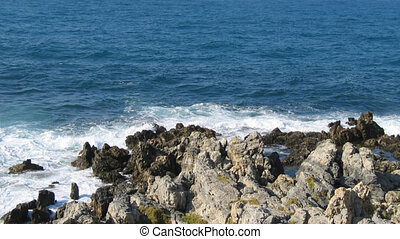 Rock on the edge of the sea, deep blue water surface with fine waves