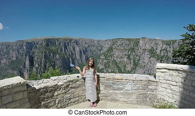 happy little girl waves with a Greek flag on Vikos gorge...