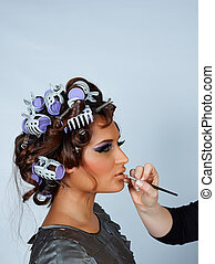 model with hair in curlers and lipstick brush. - beautiful...
