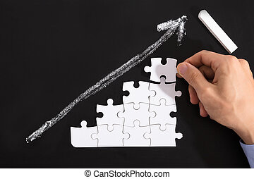 Person Arranging Puzzles On Blackboard - Close-up Of A...