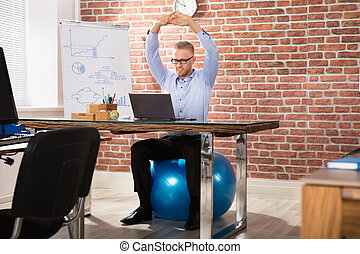 Happy Businessman Relaxing On Fitness Ball In Office