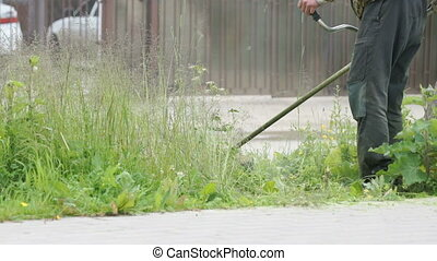 Worker cuts the grass with lawn string trimmer - The worker...