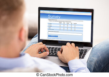 Man Filling Survey Form On Laptop - Businesswoman With...