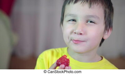 Little boy with brown hair eating a strawberry. Smiling and charismatic 4K